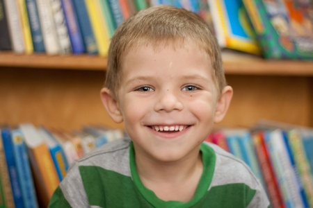 small boy smiling on the background of the books in the library