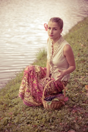 Beautiful girl in a long skirt with a basket of grapes outdoors shooting photo