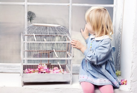 Little girl sitting on the windowsill next to a beautiful white cage and looks out the window photo