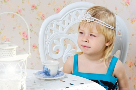 Little girl in a beautiful dress photography studio drinking tea photo