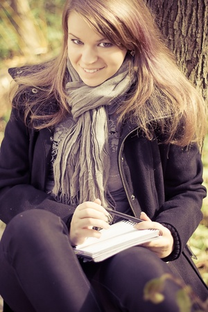 A girl writes on a pad in the park outdoors shooting Stock Photo