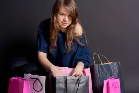 A happy girl with shopping bags after studio photography