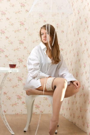 mans shirt: A girl in a mans shirt and stockings sitting on a chair studio photography
