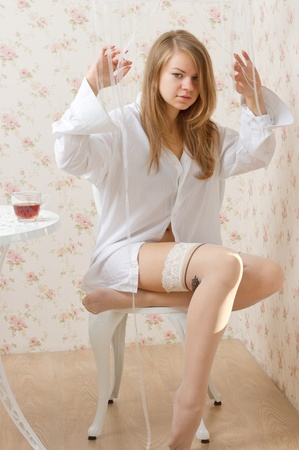 A girl in a man's shirt and stockings sitting on a chair studio photography Stock Photo - 13007041
