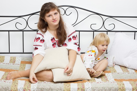 Two girls dressed in Ukrainian on the bed, studio photography Stock Photo - 13007054