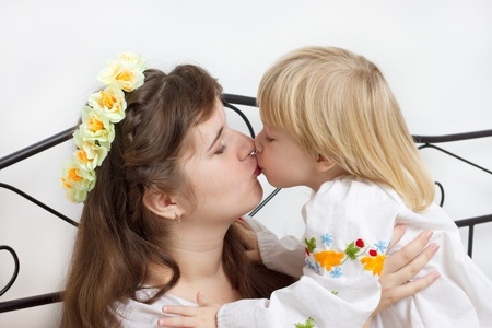 Kiss of the mother and daughter dressed in Ukrainian studio photography photo