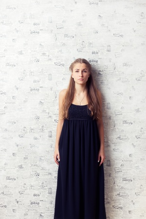 Beautiful girl in a dress near the wall studio photography