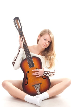Beautiful girl in sweater with a guitar studio photography photo