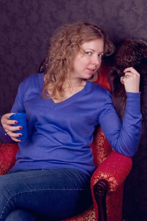 Beautiful young in a blue sweater woman sitting  photo