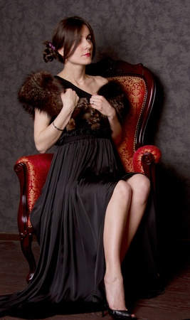 woman with dress is sitting in chair