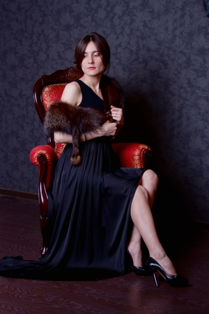 woman with dress is sitting in chair photo