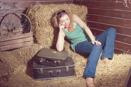 girl in the hay near the luggage studio shooting photo