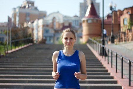 Young woman running and training in city streets photo
