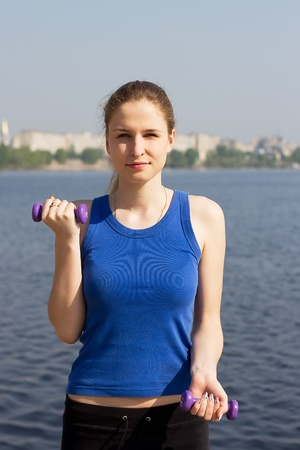 Young woman with weights exercising in the nature Healthy lifestyle and fitness concept Stock Photo - 13458570