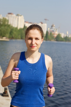 Young woman with weights exercising in the nature Healthy lifestyle and fitness concept photo