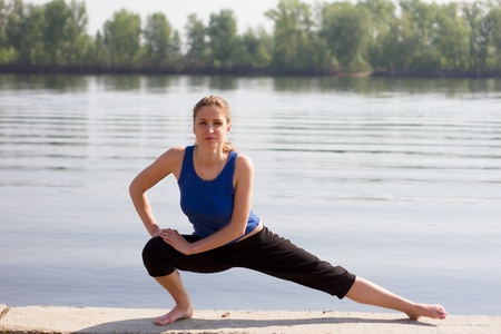 Yoga Woman on a dock by the river photo