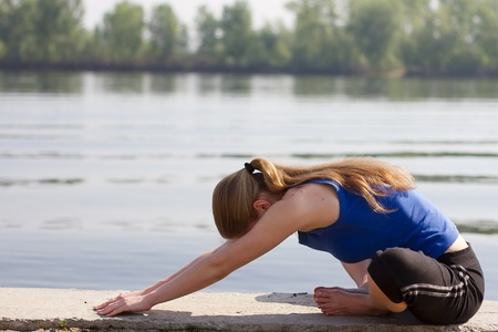 Yoga Woman on a dock by the river Stock Photo