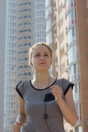 young beautiful woman listening music running in city street Stock Photo - 13458668