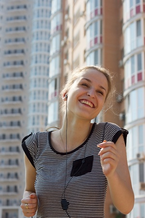young beautiful woman listening music running in city\ street