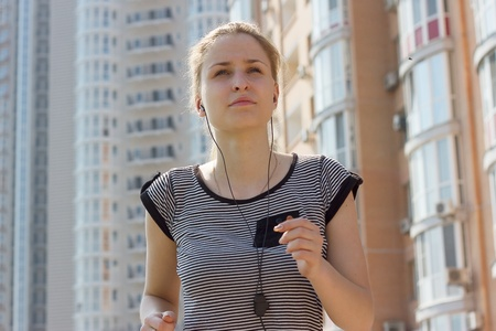 young beautiful woman listening music running in city street