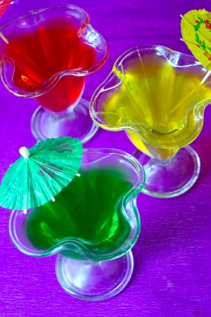 Red, green and yellow glasses with jelly on a blue background photo