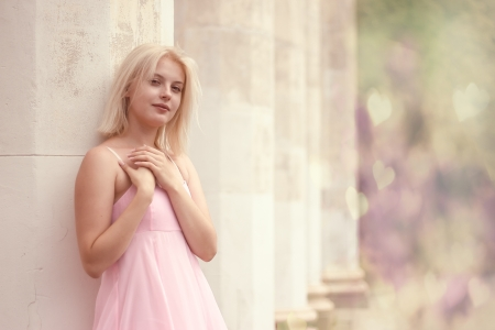 young woman in summer dress  against old stone wall, outdoor shot Stock Photo - 15044156