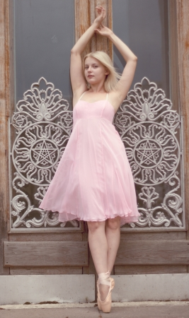 Ballerina in a pink dress posing with hands up at the door with white ornament photo
