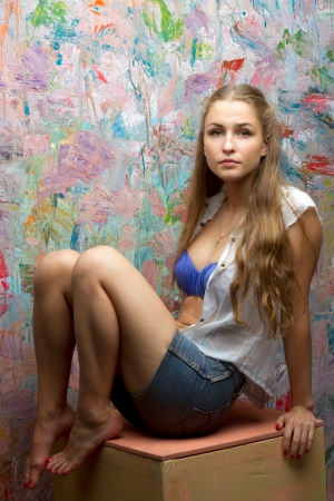 Girl with long hair sitting near colorful wall photo