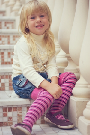Girl 3 years old in a denim skirt and pink tights sitting on a beautiful staircase photo