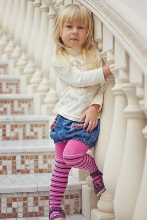 Girl 3 years old in a denim skirt and pink tights is a beautiful staircase photo