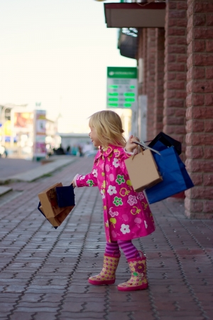 3 years old girl in a bright pink coat standing on the street with shopping Stock Photo - 15646897