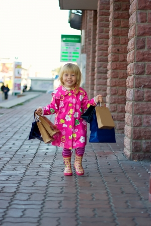 3 years old girl in a bright pink coat running down the street with shopping