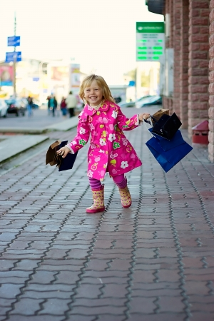 Joyful Girl 3 years in a bright pink coat running down the street with shopping photo