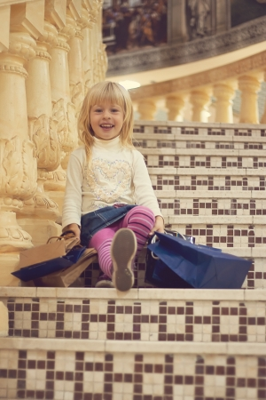Blonde girl 3 years old in bright clothes sitting on the stairs with shopping Stock Photo - 15646907