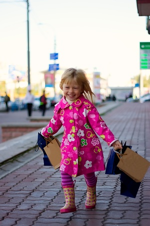 Cheerful blond girl 3 years old in a bright pink coat running down the street with shopping photo