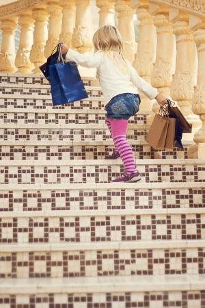 Blonde girl 3 years old in bright clothes goes up the stairs with shopping Stock Photo - 15646903