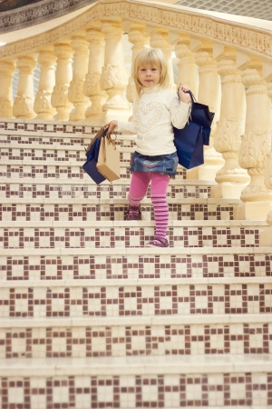 Blonde girl 3 years old in bright clothes comes down the stairs with shopping Stock Photo - 15646901