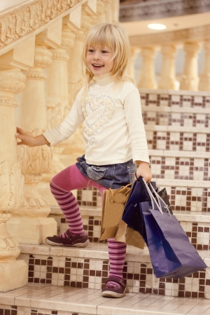 Blonde girl 3 years old in bright clothes standing on the stairs with shopping Stock Photo - 15646908