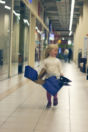 Blonde girl 3 years old in bright clothes running around the store with shopping Stock Photo - 15646902