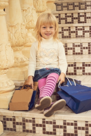 Blonde girl 3 years old in bright clothes happy sitting on the stairs with shopping Stock Photo - 15646904