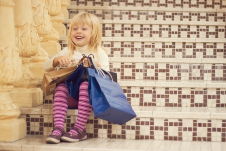Pleased blonde girl 3 years old in bright clothes sitting on the stairs with shopping