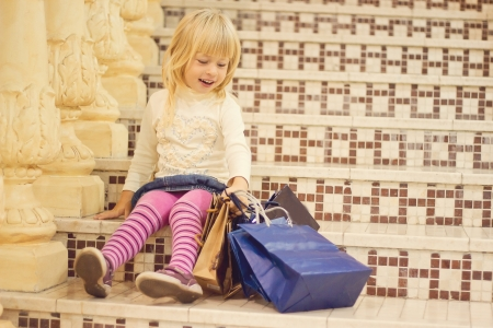 Smiling blond girl 3 years old in bright clothes sitting on the stairs with shopping Stock Photo - 15646905