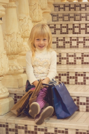 Happy blond girl 3 years old in bright clothes sitting on the stairs with shopping Stock Photo - 15646909