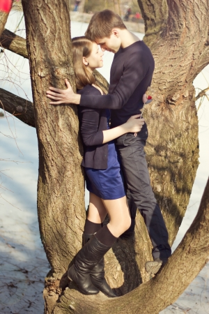 Young beautiful couple in the blue dress hugging a tree in winter