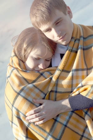 Young beautiful couple embracing in winter wrapped in a yellow blanket photo