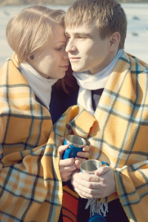 A young couple in love in winter wrapped in a yellow blanket and drink tea photo