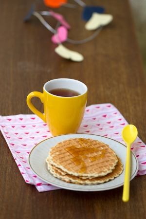 Round wafers, yellow cup with a spoon on a napkin, with a heart of paper in the background photo