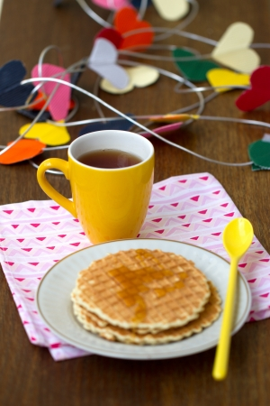 Round wafers, yellow cup with a long spoon on a napkin, with a heart of paper in the background photo