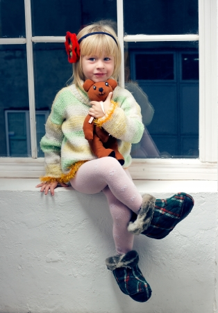 3 year old girl in knitted sweater and tights with a toy in his hand sitting on the window