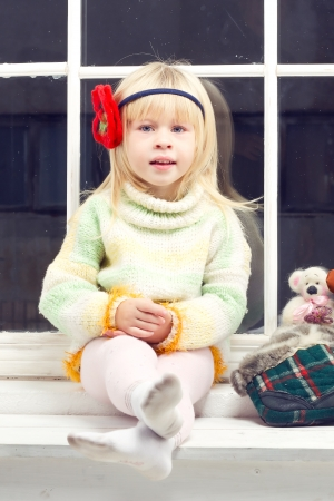 blonde little girl in knitted sweater sitting on the window and looks into the camera